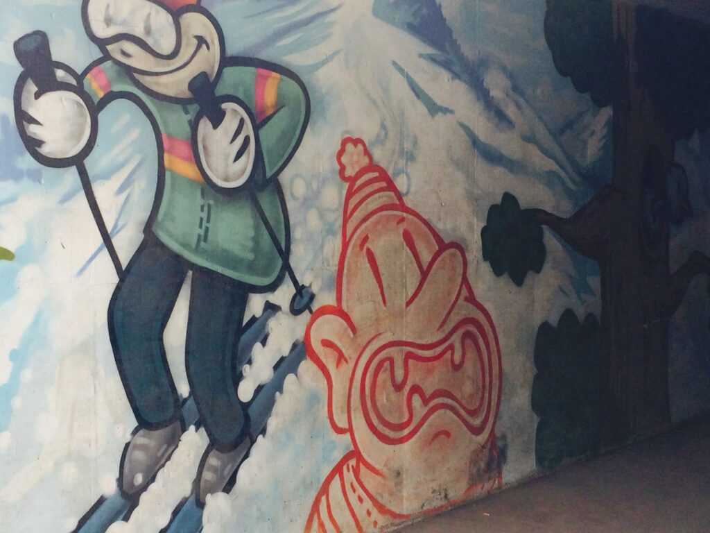 Street Art painting of a nostalgic skiers in artist Trent Call's signature cartoon style.