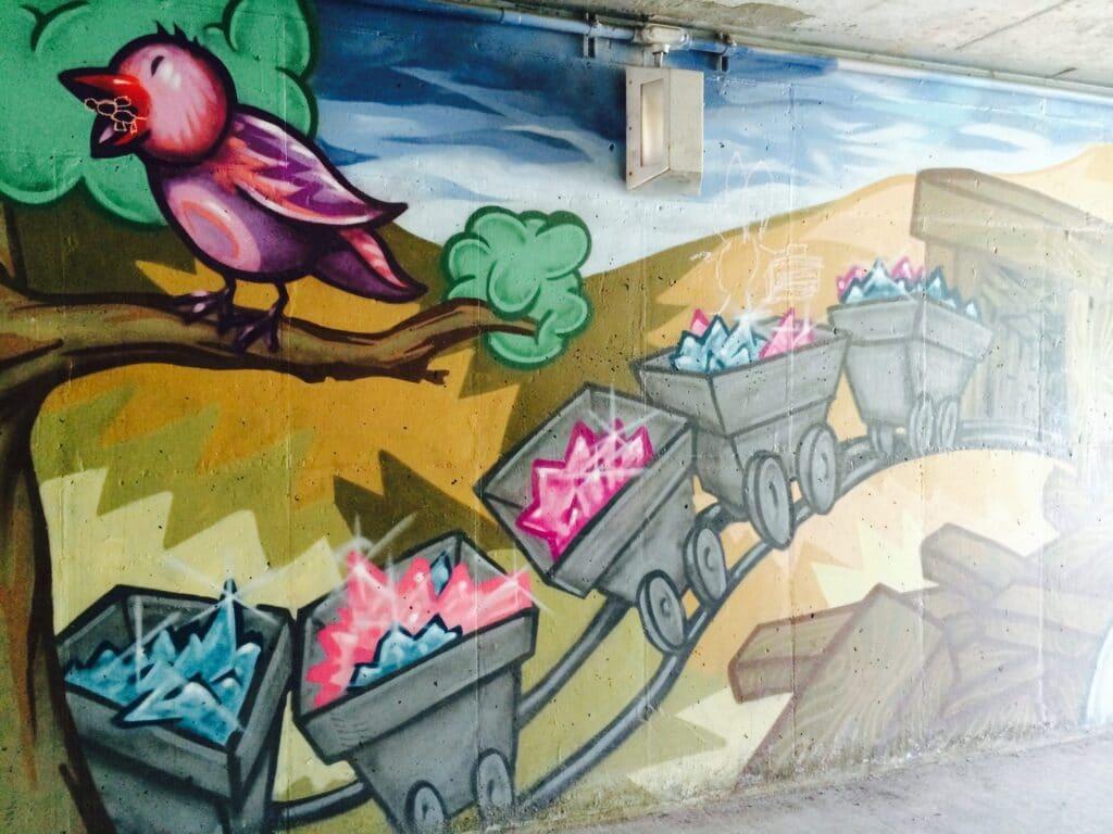 Street Art painting of a nostalgic tweety bird and mining carts in artist Trent Call's signature cartoon style.