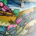 Street Art painting of a nostalgic tweety bird and mining carts in artist Trent Call's signature cartoon style.