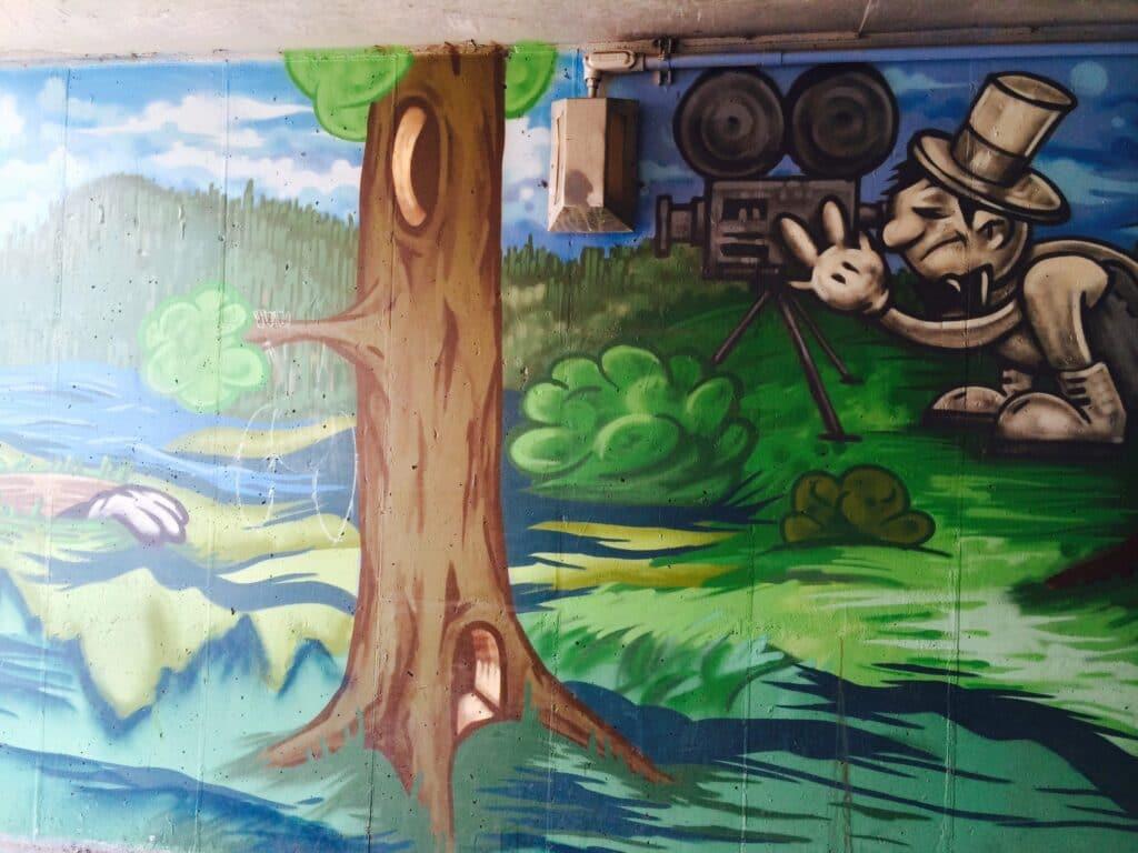 Street Art painting of a nostalgic film maker in artist Trent Call's signature cartoon style.