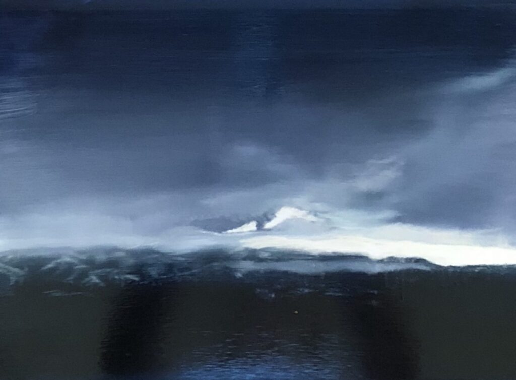 Deep blue foreground, blurry mountains and a sliver of light peeking beneath the stormy dark blue clouds.