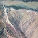 Oil painting on metal by Cynthia McLoughlin of blush colored mountain tops and blue horizon.