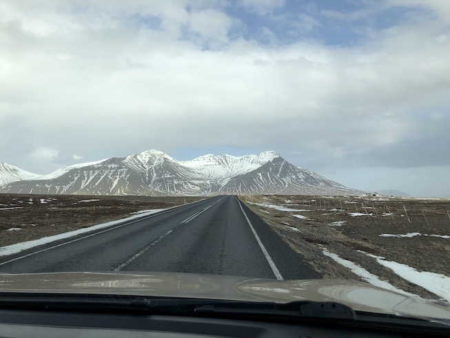 Photo of a long, straight road going straight as an arrow to the volcanic mountains of Iceland in the early spring. Snow still on the peaks but not much on the sides of the road