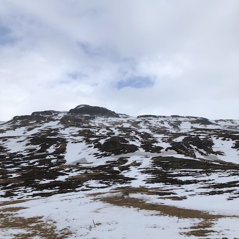 A photo of a snow spotted, volcanic, rocky mountain rising toward a blue sky with snowy white clouds.