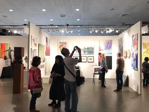 Buyers looking looking at the art in the Art UpClose booth at the LA Art Show, 2020.