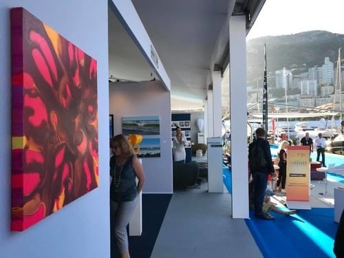 Pink, maroon and gold painting hanging on the wall of the Art UpClose booth at the Monaco Yacht Show, 2019.