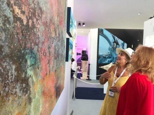 Buyers looking at multi-colored abstract paintings at the Monaco Yacht Show, 2019.