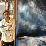 Cynthia McLoughlin in her studio in front of her painting, Celestial Rhapsody.