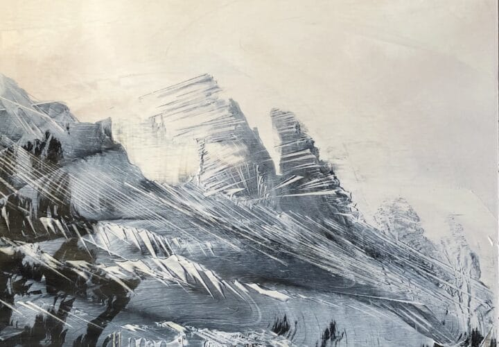 A snowy mist flows over the dark Ridgeline of the mountains.